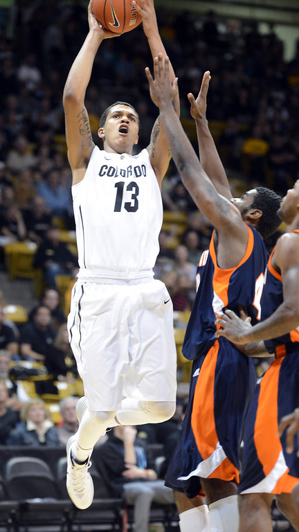 . Dustin Thomas of CU shoots past Javier Martinez, of Tenn-Martin, during the first half of the November 10, 2013 game in Boulder, Colorado. (The Daily Camera/Cliff Grassmick)