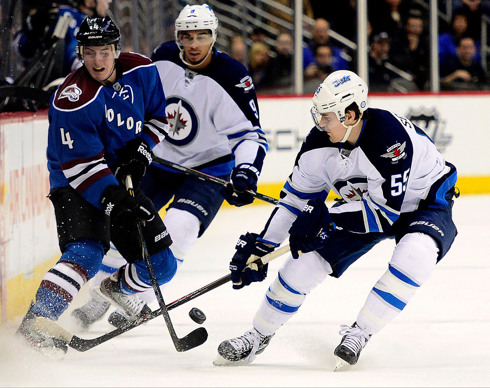 . Tyson Barrie (4) of the Colorado Avalanche clears the puck as Evander Kane (9) of the Winnipeg Jets and Mark Scheifele (55) defend during the third period of action. The Colorado Avalanche lost 2-1 to the Winnipeg Jets at the Pepsi Center on Sunday, December 29, 2013. (Photo by AAron Ontiveroz/The Denver Post)