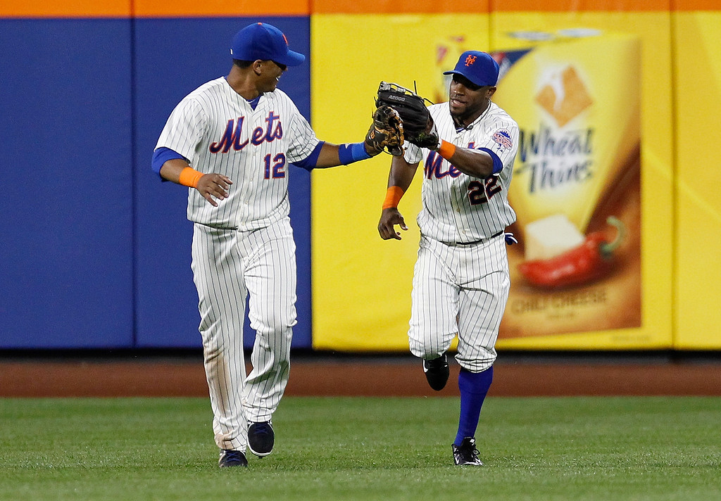 . Eric Young Jr. #22 of the New York Mets celebrates with Juan Lagares #12 after making a diving catch in the sixth inning against the Colorado Rockies at Citi Field on August 6, 2013 at Citi Field in the Flushing neighborhood of the Queens borough of New York City. Mets defeated the Rockies 3-2.  (Photo by Mike Stobe/Getty Images)