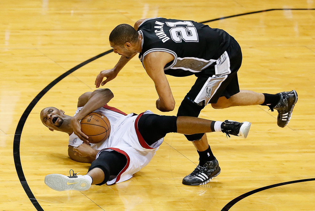. Chris Bosh #1 of the Miami Heat with the ball on the court as Tim Duncan #21 of the San Antonio Spurs goes after it in the first half during Game Six of the 2013 NBA Finals at AmericanAirlines Arena on June 18, 2013 in Miami, Florida.  (Photo by Kevin C. Cox/Getty Images)
