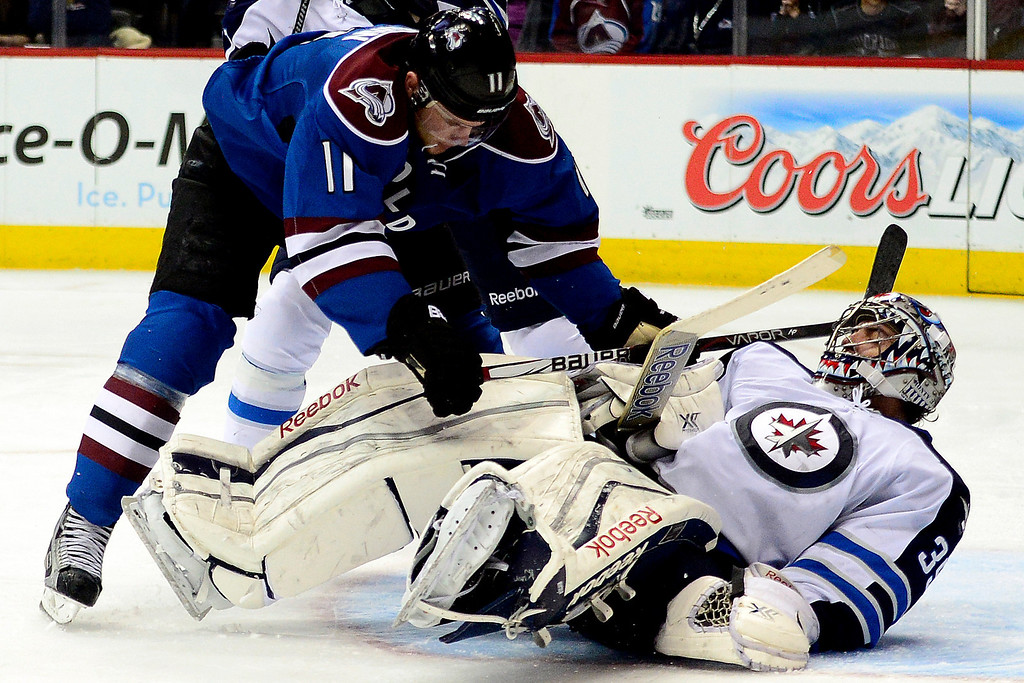. Jamie McGinn (11) of the Colorado Avalanche collides with Al Montoya during the third period of action. The Colorado Avalanche lost 2-1 to the Winnipeg Jets at the Pepsi Center on Sunday, December 29, 2013. (Photo by AAron Ontiveroz/The Denver Post)