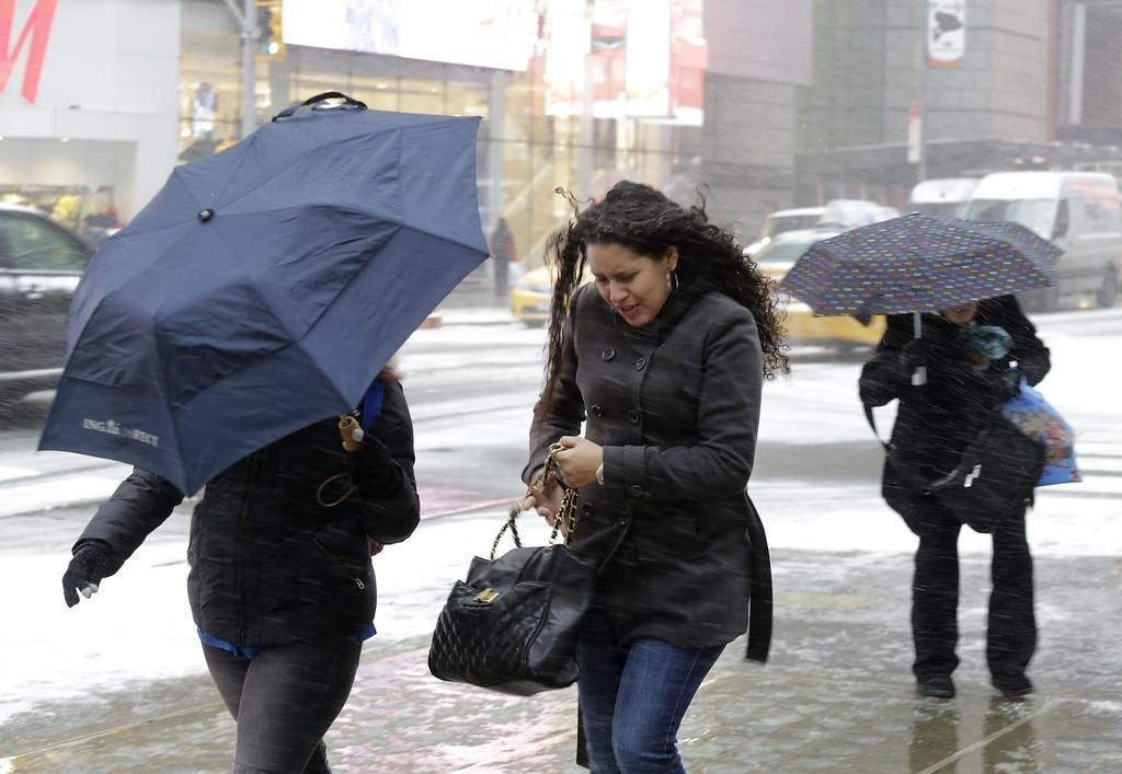 . Pedestrians make their way through a snowfall, Tuesday, Jan. 21, 2014 in New York\'s Times Square.  (AP Photo/Mark Lennihan)