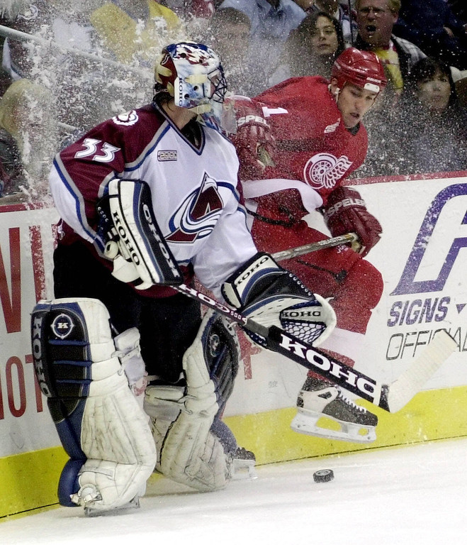 . Detroit Red Wings defenseman Mathieu Dandenault, right, runs into the boards as he tries to reach the puck before it is cleared by Colorado Avalanche goalie Patrick Roy during the first period of game 2 of the teams\' NHL Western Conference semifinal series at Denver\'s Pepsi Center on Saturday, April 29, 2000. (AP Photo/Bryan Kelsen)