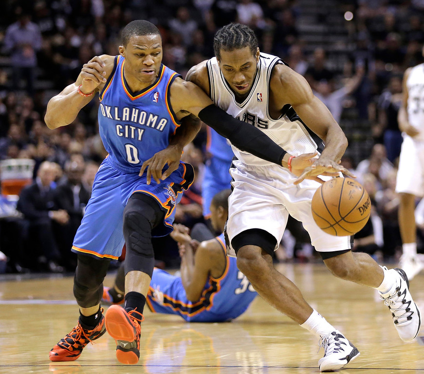 . Oklahoma City Thunder\'s Russell Westbrook (0) and San Antonio Spurs\' Kawhi Leonard chase a loose ball during the first half of Game 5 of the Western Conference finals NBA basketball playoff series, Thursday, May 29, 2014, in San Antonio. (AP Photo/Eric Gay)