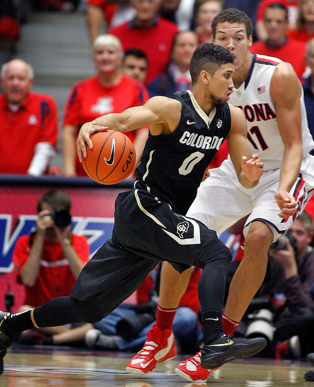 . Colorado\'s Askia Booker (0) drives pass the attempted defense of Arizona\'s Aaron Gordon (11) in the first half of an NCAA college basketball game, Thursday, Jan. 23, 2014 in Tucson, Ariz. (AP Photo/John Miller)