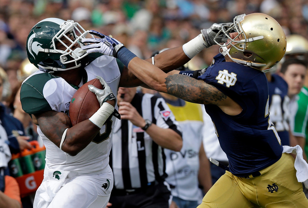 . Michigan State running back Jeremy Langford, left, battles with Notre Dame cornerback Bennett Jackson to pick up yardage during the first half of an NCAA college football game in South Bend, Ind., Saturday, Sept. 21, 2013. (AP Photo/Michael Conroy)