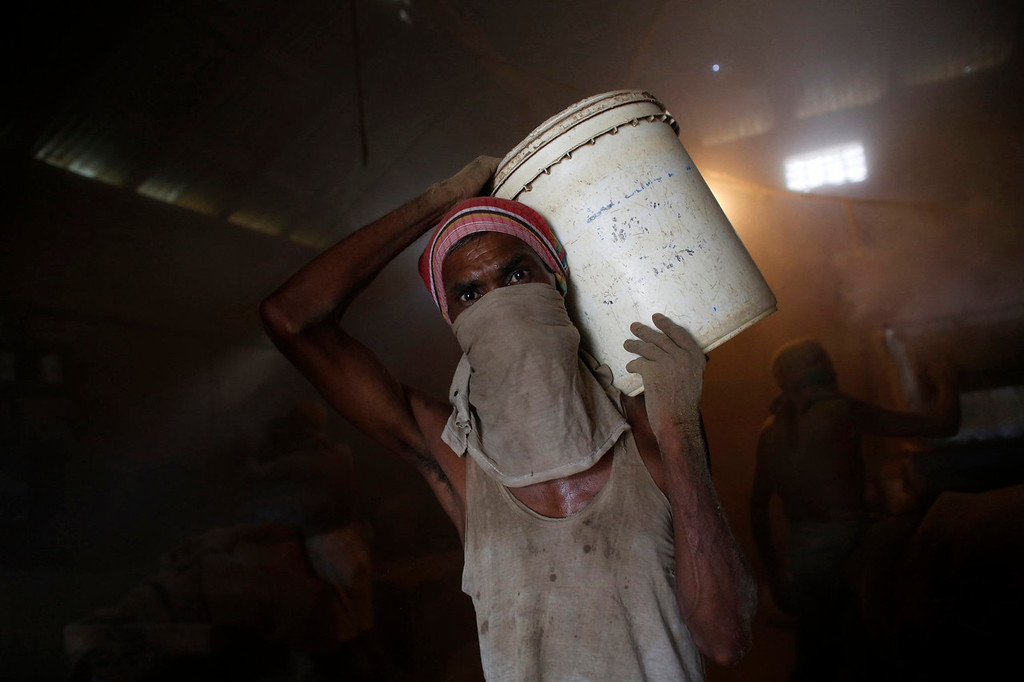 ". A worker carries a bucket while he works in a small bidi (cigarette) factory at Haragach in Rangpur district, Bangladesh July 13, 2013. According to a 2012 study by US-based NGO, Campaign for Tobacco-Free Kids, over 45,000 people in Bangladesh are employed in manufacturing inexpensive cigarettes known as bidis and this number includes ""many women and children working in household based establishments where they make low wages and live in poverty.\"" A 2011 research paper about bidi workers in Bangladesh, published in the journal Tobacco Control, says that working conditions can involve poor ventilation and exposure to tobacco dust, which can cause a range of health problems including respiratory and skin diseases. International attention has been focused on workers\' safety in Bangladesh since the disaster at Rana Plaza, a garment factory complex which collapsed in April, killing 1,132 workers.   REUTERS/Andrew Biraj"