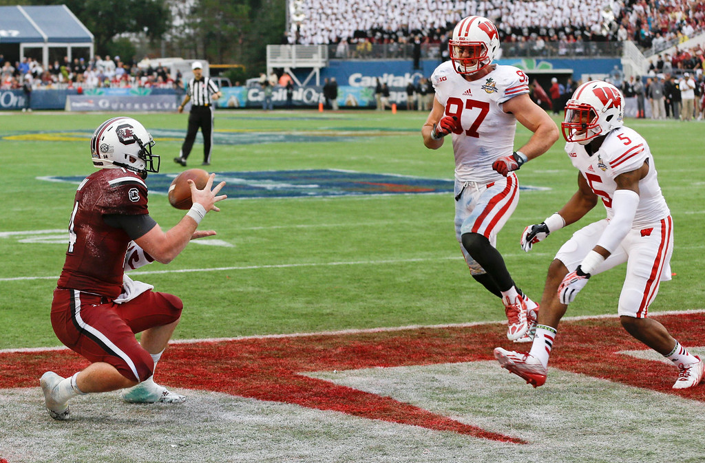 . South Carolina quarterback Connor Shaw, left, catches a touchdown pass in the end zone from receiver Bruce Ellington as Wisconsin cornerback Darius Hillary (5) and linebacker Brendan Kelly (97) attempt to defend during the first half of the Capital One Bowl NCAA college football game in Orlando, Fla., Wednesday, Jan. 1, 2014.(AP Photo/John Raoux)