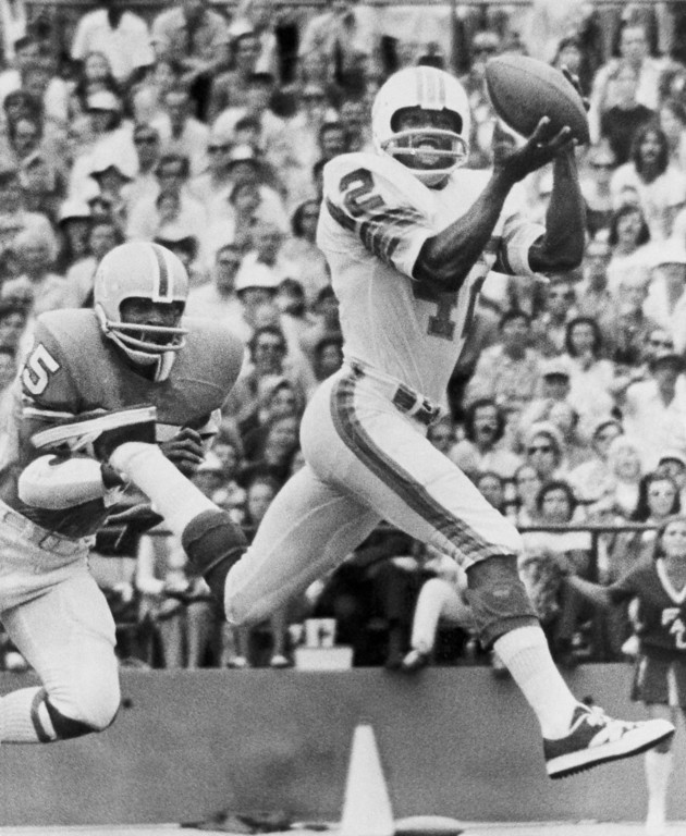 . Wide receiver Paul Warfield of the Miami Dolphins pulls in a pass from Bob Griese in National Football League action against the Houston Oilers in second quarter on a rainy at the Orange Bowl in Miami on Sunday, Sept. 24, 1972. Trying to reach Warfield is John Charles of the Oilers. (AP Photo)