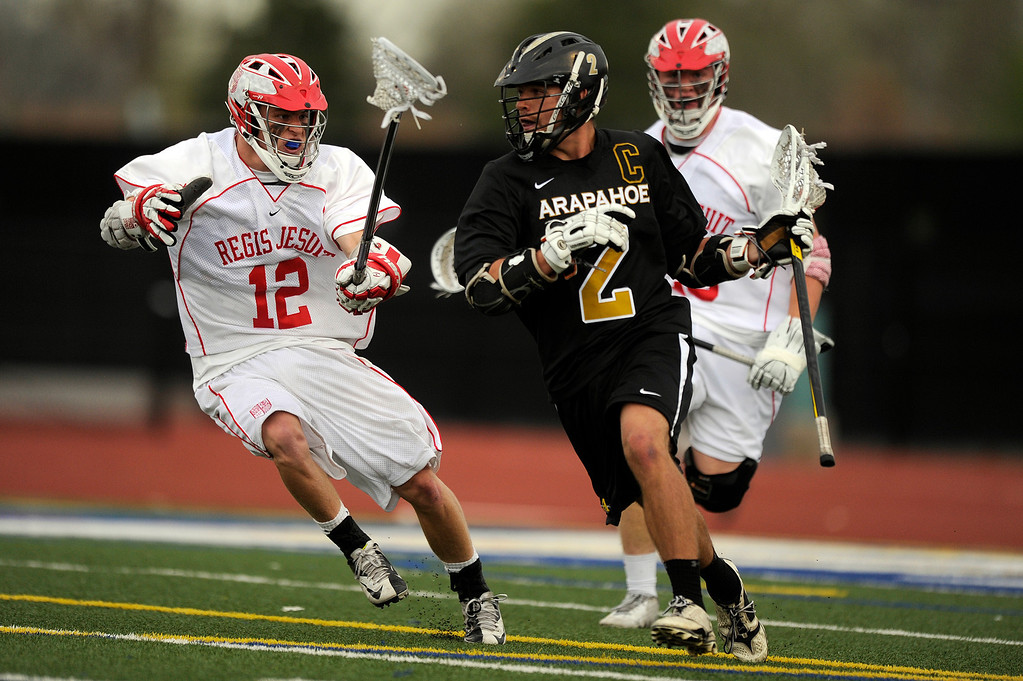 . DENVER, CO - MAY 15: Arapahoe High School senior midfielder Michael Babb #2 dodges Regis Jesuit junior defenseman Will Deines #12 during the first quarter of a CHSAA 5A boys lacrosse semifinal game on May 15, 2013, in Denver, Colorado. Arapahoe won 13-5 to advance to the finals. (Photo by Daniel Petty/The Denver Post)