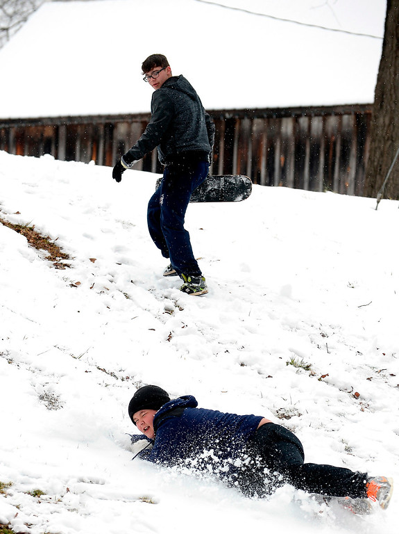 ". Micah Hulit, center, falls down in the snow as he and Aaron Warren slide down a hill in a winter snow storm that the National Weather Service predicted to be ""an event of historical proportions\"" blows into Georgia\'s Bartow County in Euharlee, Ga., about 40 miles north of metro Atlanta, on Tuesday, Feb. 11, 2014. (AP Photo/David Tulis)"