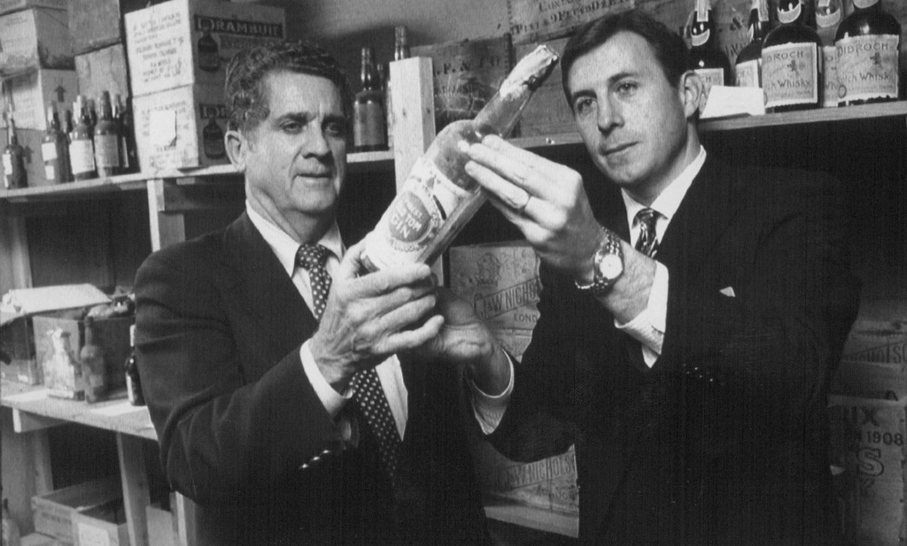 . FEB 12 1992 - Lonnie Lantz, left, and Craig Reed examine a bottle of old gin earlier this month that was stashed in the vault at the Broadmoor Hotel in Colorado Springs, Colo., during Prohibition. This was one of 629 bottles, including a 142-year-old bottle of wine, that Spencer Penrose, founder of the Broadmoor Hotel, double locked in a vault under the pool. 1992. (Credit: AP Photo)