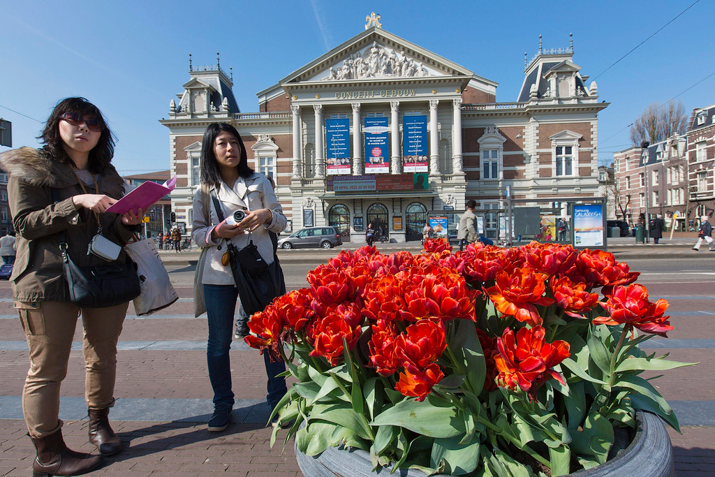. Two Japanese tourists look at a city map in front of the Concertgebouw music theater on the Museum square in Amsterdam April 24, 2013. The Royal celebrations in the Netherlands this week put the country and the capital Amsterdam on front pages and television screens around the world with an orange splash. There\'s plenty to see and do in 48 hours in this compact city, where the world-famous Rijksmuseum only recently reopened after an extensive renovation. Picture taken April 24, 2013. REUTERS/Michael Kooren
