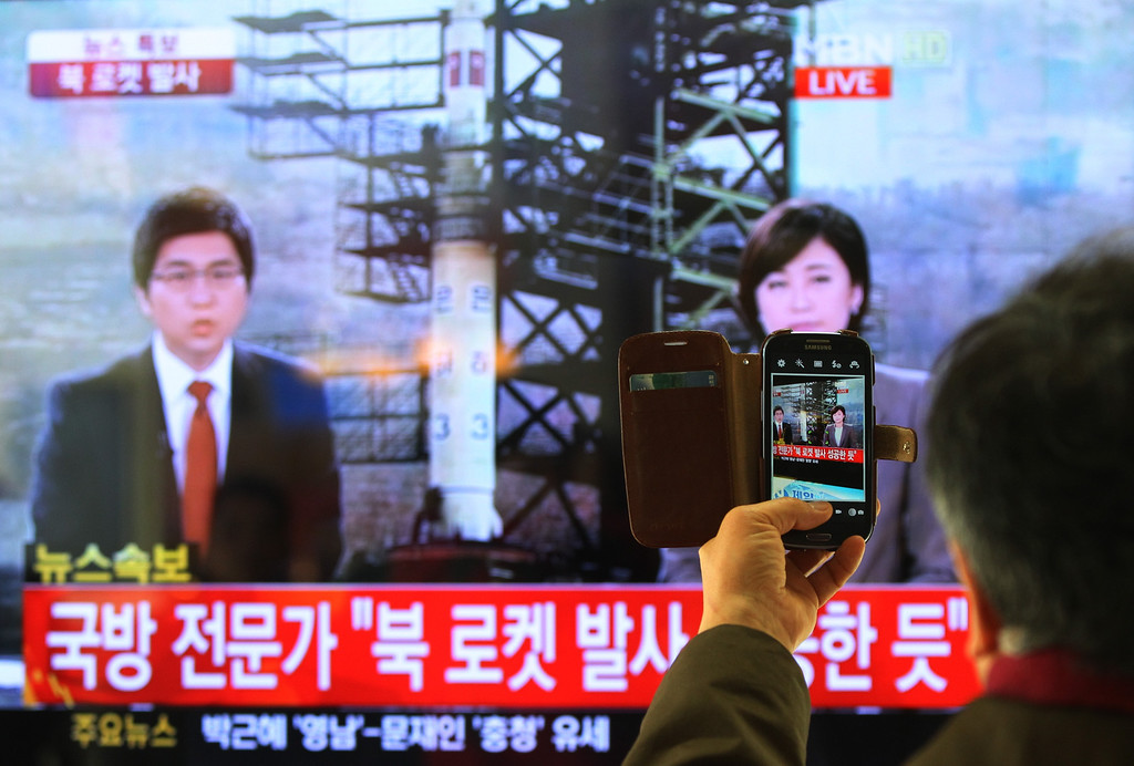 """. South Korean man uses his smartphone to take a television screen reporting a news about North Korea\'s rocket launch at Seoul Railway Station in Seoul, South Korea, Wednesday, Dec. 12, 2012. North Korea fired a long-range rocket Wednesday in its second launch under its new leader, South Korean officials said, defying warnings from the U.N. and Washington only days before South Korean presidential elections. The letters on the screen read \"""" North Korea\'s rocket launch seems to be successful.\"""" (AP Photo/Ahn Young-joon)"""