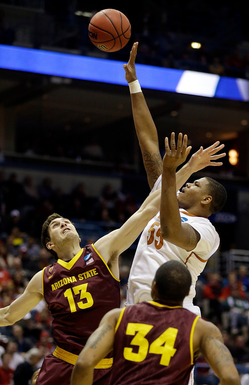. Texas center Cameron Ridley (55) takes shot against Arizona State center Jordan Bachynski (13) and guard Jermaine Marshall (34) during the first half of a second-round game in the NCAA college basketball tournament Thursday, March 20, 2014, in Milwaukee. (AP Photo/Jeffrey Phelps)