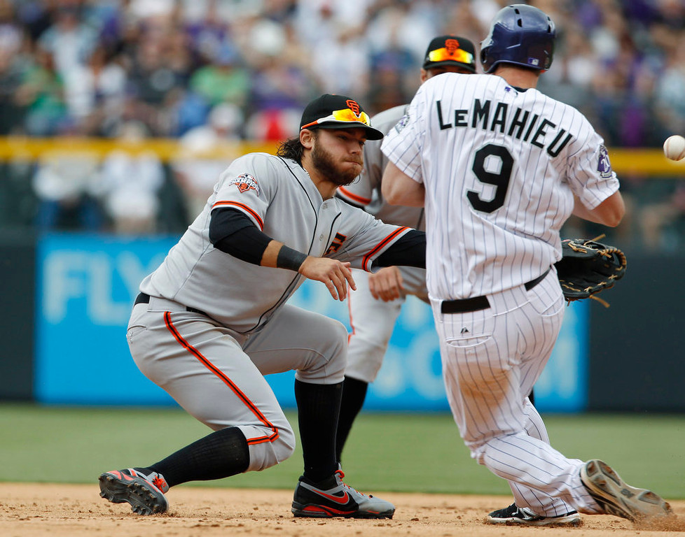 . San Francisco Giants shortstop Brandon Crawford, left, tries to field throw as Colorado Rockies\' DJ LaMahieu (9) advances to second base in the fifth inning of a baseball game in Denver, Sunday, May 19, 2013. (AP Photo/David Zalubowski)