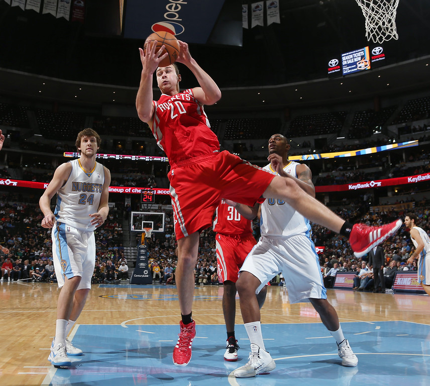. Houston Rockets forward Donatas Motiejunas, center, of Lithuania, pulls down a rebound as Denver Nuggets forwards Jan Vesely, left, of the Czech Republic, and Darrell Arthur cover in the fourth quarter of the Nuggets\' 123-116 victory in an NBA basketball game in Denver on Wednesday, April 9, 2014. (AP Photo/David Zalubowski)
