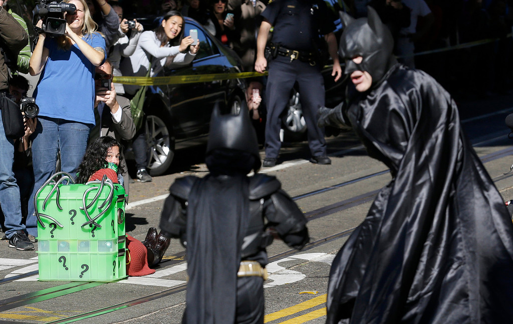 """. Miles Scott, dressed as Batkid, center, walks with Batman to save a damsel in distress on the Cable Car line in San Francisco, Friday, Nov. 15, 2013.  San Francisco turned into Gotham City on Friday, as city officials helped fulfill Scott\'s wish to be \""""Batkid.\"""" Scott, a leukemia patient from Tulelake in far Northern California, was called into service on Friday morning by San Francisco Police Chief Greg Suhr to help fight crime, The Greater Bay Area Make-A-Wish Foundation says. (AP Photo/Jeff Chiu)"""