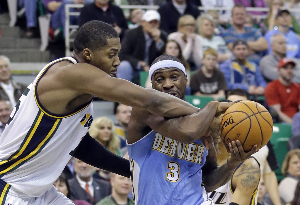 . Utah Jazz\'s Derrick Favors, left, fouls Denver Nuggets\' Ty Lawson (3) in the second half during an NBA basketball game Monday, Jan. 13, 2014, in Salt Lake City. The Jazz won 118-103. (AP Photo/Rick Bowmer)