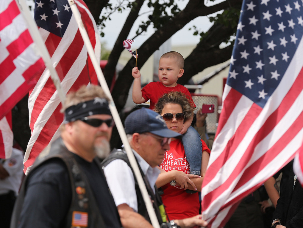 . Heather Heim holds up her three year-old son, Grady,  while members of the Patriot Guard march in a processional to a memorial service for first responders who died in last week\'s fertilizer plant explosion in West, Texas, Thursday, April 25, 2013, in Waco, Texas.   (AP Photo/Waco Tribune Herald, Rod Aydelotte)