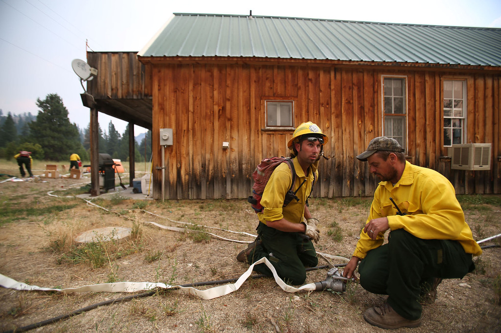 . Chris Corbus, left, and Rick Van Meer, of the Mountain Home Fire Department, prepare to defend homes from the more than 80,000-acre Elk Fire Complex burning near Pine, Idaho, Monday Aug. 12, 2013.  Pine and neighboring Featherville were under mandatory evacuation orders Monday, a day after Elmore County sheriff\'s deputies went from house to house, knocking on doors to alert residents to clear out of the area. (AP Photo/Times-News, Ashley Smith)