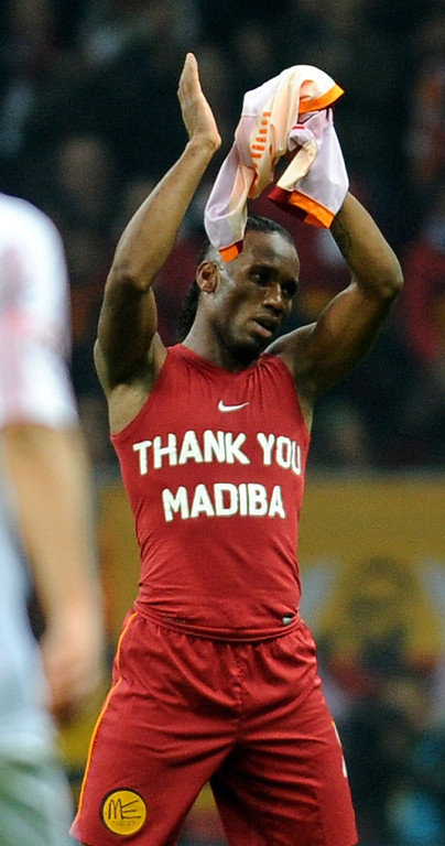 ". Galatasaray`s Didier Drogba from Ivory Coast wears a t-shirt with text reading ""Thank you Madiba\"" in honor of late former South African President Nelson Mandela, during a Turkish super league match between Galatasaray and Elazigspor match on December 6, 2013, at Turk Telekom Arena, in Istanbul. People gathered in cities around the world to make their own personal tributes to Nelson Mandela on December 6, leaving flowers and setting up makeshift shrines in an outpouring of emotion for South Africa\'s anti-apartheid icon. AFP PHOTO/STRSTR/AFP/Getty Images"