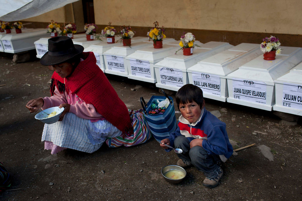 . A woman and a child eat lunch in front of a row of coffins containing the remains of villagers slain by insurgents nearly three decades ago, in Chaca, Peru. The remains were exhumed in 2012 from a mass grave and released to family members June 13, 2013. Peru has failed to address the unhealed wounds of thousands of families, most of them poor, Quechua-speaking peasants, traumatized by the country\'s 1980-2000 conflict.   (AP Photo/Rodrigo Abd)