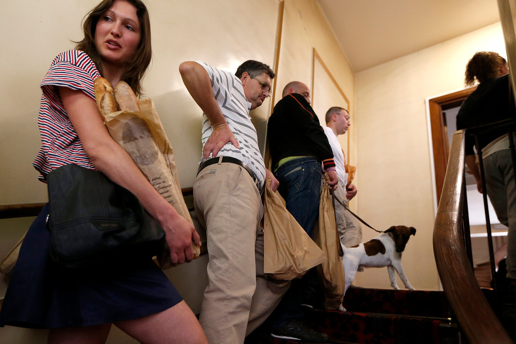 . Bakers carrying baguettes, French bread, wait in the stairway to register in the competition for the \'Grand Prix de la Baguette de la Ville de Paris\' (Best Baguette of Paris 2013) annual prize at the Chambre Professionnelle des Artisans Boulangers Patissiers in Paris April 25, 2013. The baguette is a French cultural symbol par excellence and the competition saw 203 Parisian bakers who compete for recognition as finest purveyor of one of France\'s most iconic staples. The baguettes are registered, given anonymous white wrappings and an identification number. They are then carefully weighed and measured to ensure they do not violate the contest\'s strict rules. 52 entries were withdrawn for failing to measure between 55-70cm long or not matching the acceptable weight of between 250-300g. Every year, the winner earns the privilege of baking bread for the French President.   REUTERS/Charles Platiau