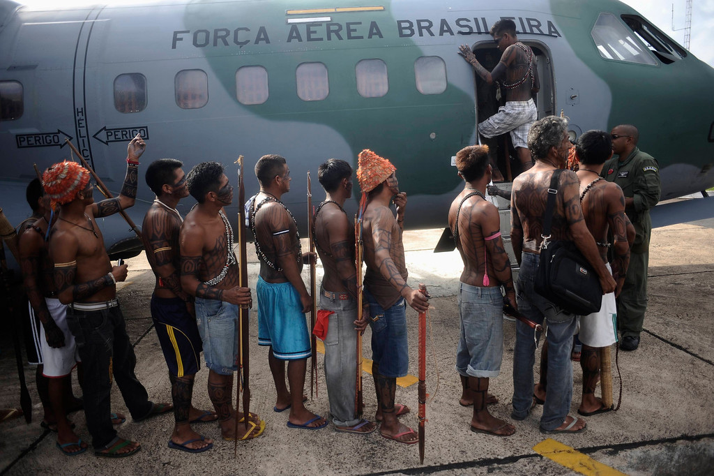 . Munduruku Indians, many of who are flying for the first time, board a Brazilian Air Force plane to fly to Brasilia for talks with the government, in Altamira June 4, 2013. Air Force planes flew 144 Munduruku Indians to Brasilia for talks to end a week-long occupation of the controversial Belo Monte dam on the Xingu River, a huge project aimed at feeding Brazil\'s fast-growing demand for electricity. REUTERS/Lunae Parracho
