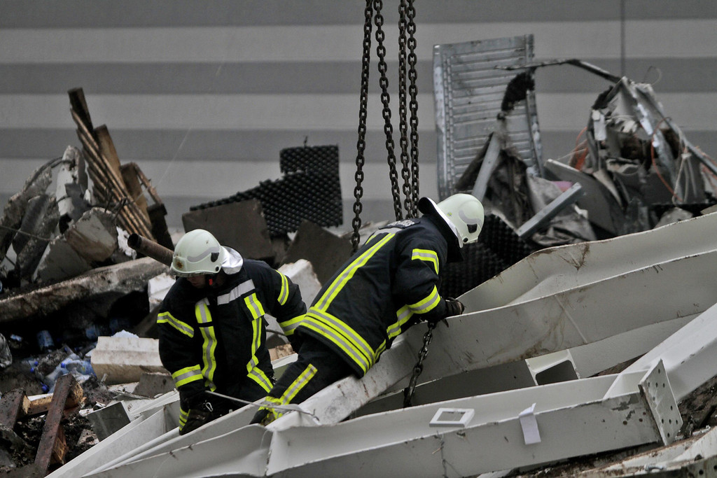 . Rescue helpers sift through parts of the roof construction as rescue works are continued at the site of the 21 November \'Maxima\' supermarket roof collapse in Riga, 23 November 2013. EPA/VALDA KALNINA