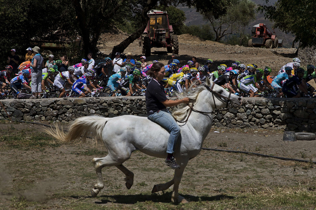 . The pack ride behind a woman riding a horse during the 156 km second stage of the 100th edition of the Tour de France cycling race on June 30, 2013 between Bastia and Ajaccio, on the French Mediterranean Island of Corsica.     JEFF PACHOUD/AFP/Getty Images