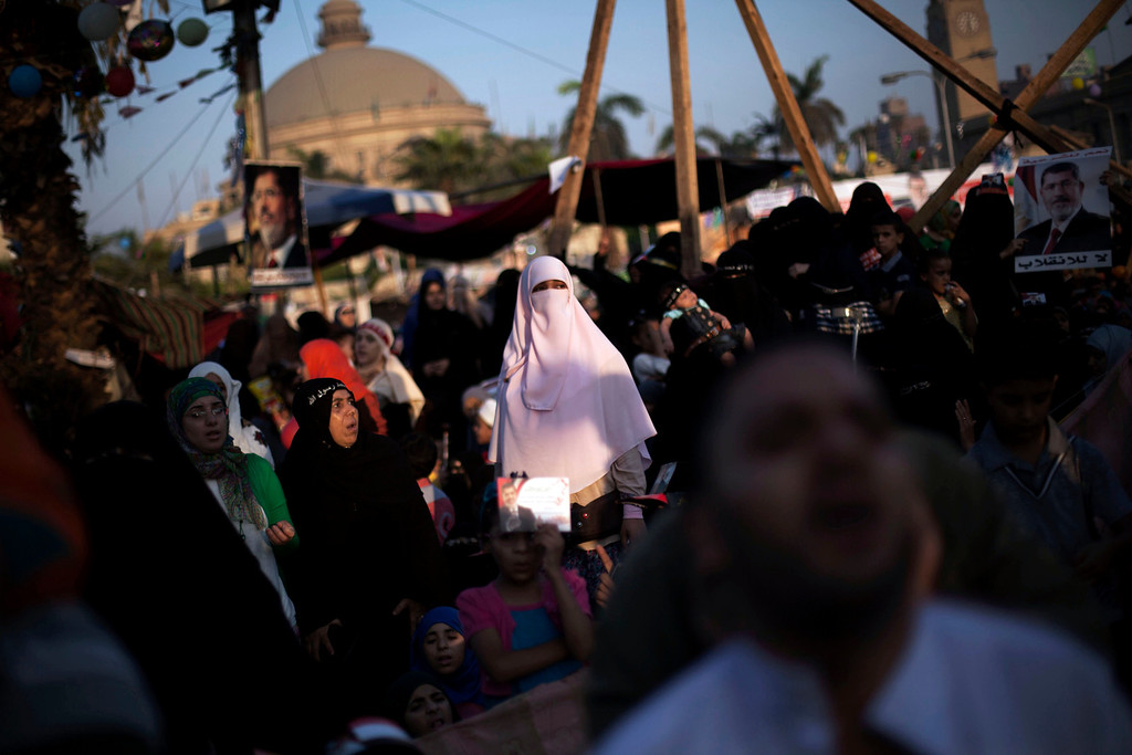 ". An Egyptian woman, a supporter of Egypt\'s ousted President Mohammed, is seen before the morning pray during the celebration of the ""Eid al-Fitr\"" holiday (end of Ramadan) near Cairo University in Giza, Egypt, Thursday, Aug. 8, 2013. This year\'s holiday is overshadowed by the deep divisions in Egypt, with the interim government planning to celebrate the feast with outdoor prayers and protests in town center squares and Morsi\'s supporters marking the holiday with their own protests and prayers, including at the two major sit-ins by the Islamists in Cairo. (AP Photo/Manu Brabo)"