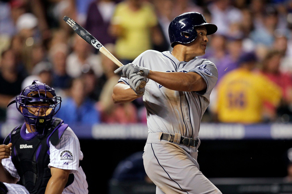 . San Diego Padres Will Venable breaks his bat as he hits a single in the sixth inning of a baseball game against the Colorado Rockies in Denver on Tuesday, Aug. 13, 2013. Rockies catcher Wilin Rosario watches. (AP Photo/Joe Mahoney)