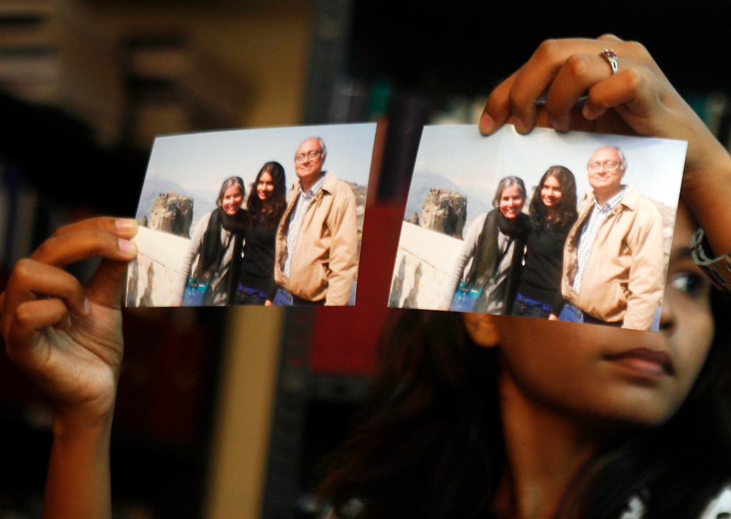. Photographs showing one of the passengers of the missing Malaysian Airlines aircraft Chandrika Sharma, left, her husband Narendran and daughter Meghna, are displayed during a press conference in Chennai, India, Wednesday, March 12, 2014. Narendran criticized the Indian government for its \'silence\' and said no government official has contacted them on the incident yet, according to a local news agency. (AP Photo/Arun Sankar K)