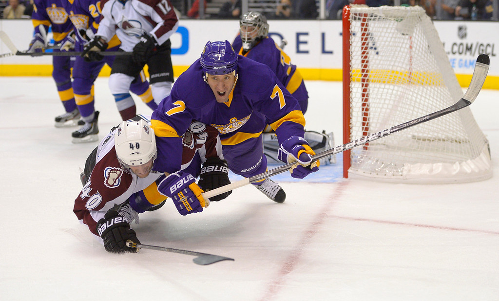 . Colorado Avalanche center Mark Olver, left, and Los Angeles Kings defenseman Rob Scuderi dive for a puck during the first period of their NHL hockey game, Saturday, Feb. 23, 2013, in Los Angeles. The Lakers won 111-107. (AP Photo/Mark J. Terrill)