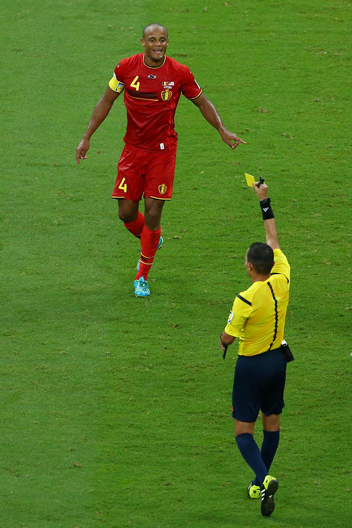 . Vincent Kompany of Belgium is shown a yellow card by referee Djamel Haimoudi during the 2014 FIFA World Cup Brazil Round of 16 match between Belgium and the United States at Arena Fonte Nova on July 1, 2014 in Salvador, Brazil.  (Photo by Robert Cianflone/Getty Images)