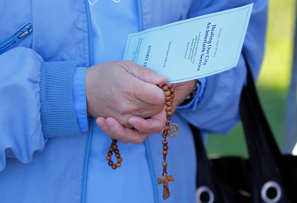 . A nun holds a pair of rosary beads along with her ticket as she waits to enter the Cathedral of the Holy Cross where U.S. President Barack Obama is scheduled to attend an interfaith service for the victims of the Boston Marathon bombings in Boston, Massachusetts April 18, 2013.   REUTERS/Jessica Rinaldi
