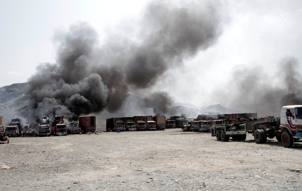 . Smoke rises from NATO supply trucks following an attack by militants in the Torkham area near the Pakistan-Afghanistan border east of Kabul, Afghanistan, Monday, Sept. 2, 2013. The Taliban claimed responsibility for the strike on a U.S. base in Afghanistan near the border with Pakistan on Monday, setting off bombs, torching vehicles and shutting down a key road used by NATO supply trucks, officials said. Several people were killed.   (AP Photo/Rahmat Gul)