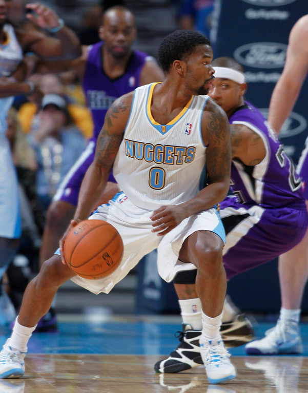 . Denver Nuggets guard Aaron Brooks (0) picks up a loose ball as Sacramento Kings guard Isaiah Thomas covers in the first quarter of an NBA basketball game in Denver on Sunday, Feb. 23, 2014. (AP Photo/David Zalubowski)
