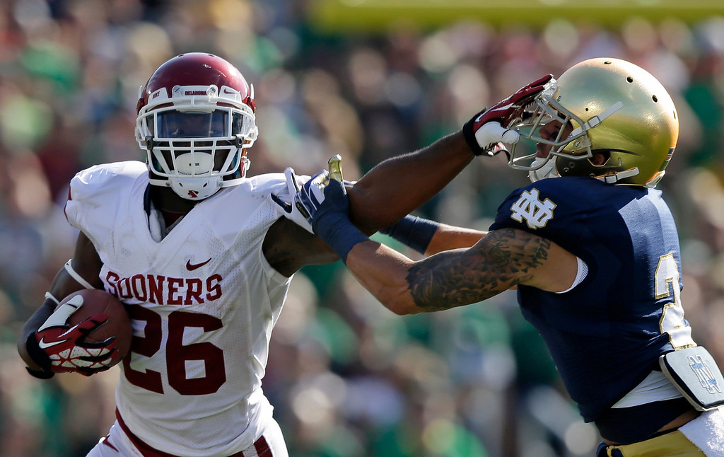 . Oklahoma\'s Damien Williams (26) runs out of the tackle of Notre Dame\'s Bennett Jackson (2) during the first half of an NCAA college football game on Saturday, Sept. 28, 2013, in South Bend, Ind. (AP Photo/Darron Cummings)