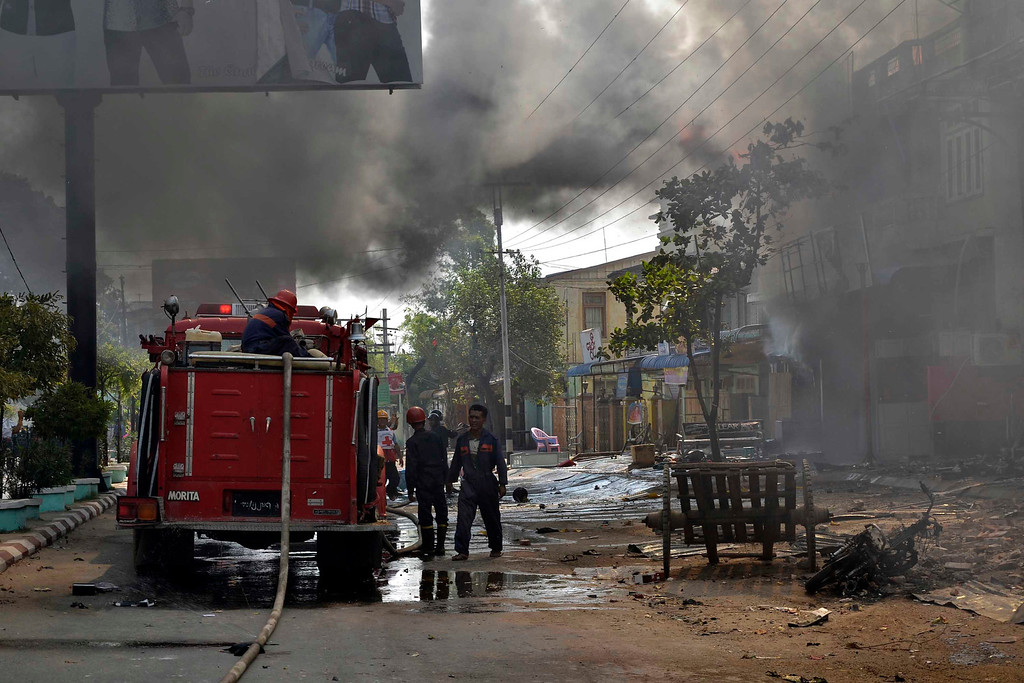 . Myanmar firefighters battle fires in burning buildings following ethnic unrest between Buddhists and Muslims in Meikhtila, Mandalay division, about 550 kilometers (340 miles) north of Yangon, Myanmar, Friday, March 22, 2013. (AP Photo/Khin Maung Win)