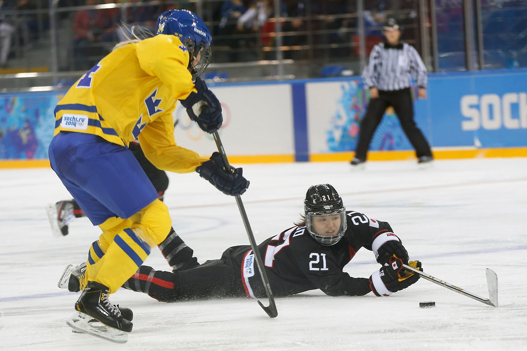 . Hanae Kubo of Japan tries to gain control of the puck under pressure from Erika Grahm of Sweden during the second period of the 2014 Winter Olympics women\'s ice hockey game at Shayba Arena, Sunday, Feb. 9, 2014, in Sochi, Russia. (AP Photo/Petr David Josek)
