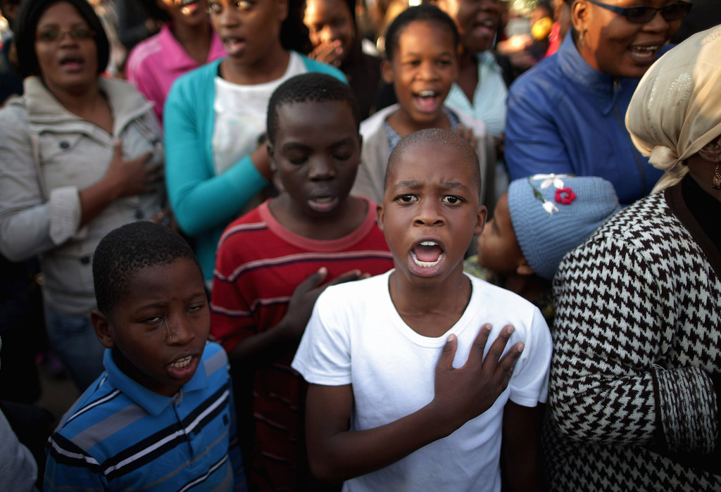 . PRETORIA, SOUTH AFRICA - JUNE 25:  A large crowd of supporters sings the South African national anthem outside of the Mediclinic Heart Hospital where former South African President Nelson Mandela is being treated June 25, 2013 in Pretoria, South Africa. South African President Jacob Zuma confirmed on June 23 that Mandela\'s condition has become critical since he was admitted to the hospital over two weeks ago for a recurring lung infection.  (Photo by Chip Somodevilla/Getty Images)