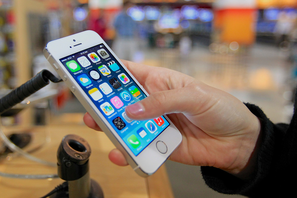 . A customer examines a new iPhone 5s at the Nebraska Furniture Mart in Omaha, Neb., on Friday, Sept. 20, 2013, the day the new iPhone 5c and 5s models go on sale. (AP Photo/Nati Harnik)