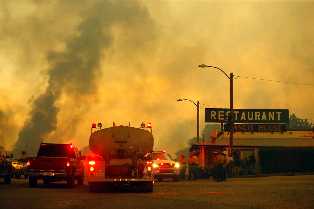 . Firefighters monitor a restaurant as the Yarnell Hill Fire burns on Sunday, June 30, 2013 near Yarnell, Ariz. The fire started Friday and picked up momentum as the area experienced high temperatures, low humidity and windy conditions. It has forced the evacuation of residents in the Peeples Valley area and in the town of Yarnell. (AP Photo/The Arizona Republic, David Kadlubowski)