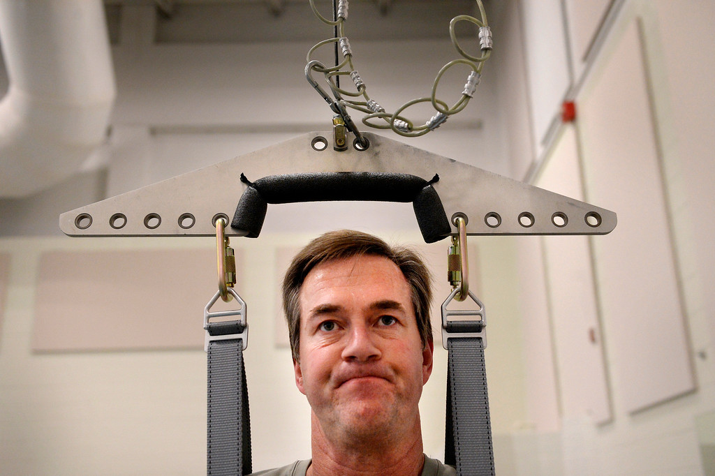 ". Suspended in a harness Kyle works out on the TheraStride at Craig Hospital. He remembers that earlier in his recovery, ""I called that machine my nemesis. I\'d take two steps and trip, take two steps and trip... I won\'t say that I\'m friends with the treadmill, but we\'re not archenemies anymore.\""  (Photo By Craig F. Walker / The Denver Post)"