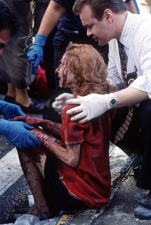 . Emergency workers help a women after she was injured in the terrorist attack on the World Trade Center in New York, Tuesday, Sept. 11, 2001. (AP Photo/Gulnara Samoilova)