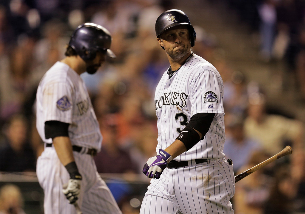 . Colorado Rockies\' Michael Cuddyer, right, walks to the dugout past Rockies\' Todd Helton after striking out in the ninth inning against the Philadelphia Phillies during of a baseball game on Friday, June 14, 2013, in Denver. Philadelphia won 8-7. (AP Photo/Joe Mahoney)