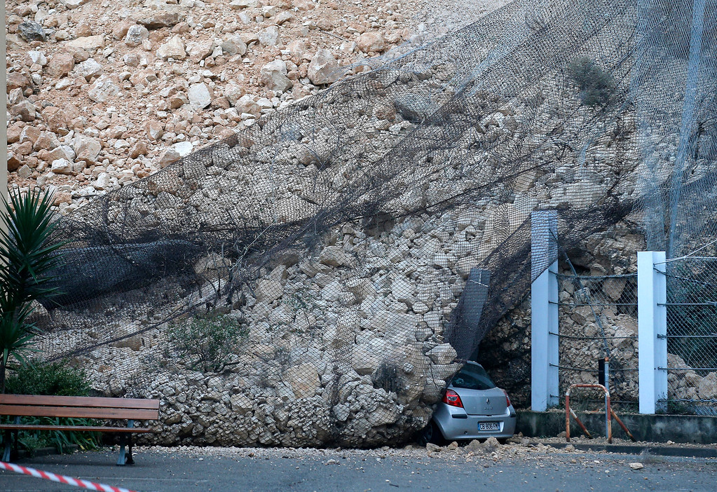 . A car parked outside a factory is covered in debris following a rockfall caused by heavy rain in La Londe Les Maures, near Toulon, southern France, Monday, Jan. 20, 2014. Unusually heavy rains have flooded the French Riviera, leaving two people dead and thousands without electricity or access to roads. (AP Photo/Lionel Cironneau)