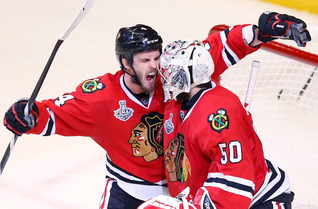 . Chicago Blackhawks\' Niklas Hjalmarsson (L) celebrates with goalie Corey Crawford after the Blackhawks defeated the Boston Bruins in Game 5 of their NHL Stanley Cup Finals hockey series in Chicago, Illinois, June 22, 2013.  REUTERS/Jim Young
